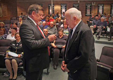 CC Dan Bisher (l), President of the Hillsdale County, MI Veterans Hall of Fame presented a Hall of Fame challenge coin to World War II P-38 pilot Monty Powers during a recent ceremony.  (photo by Corey Murray, courtesy of the Hillsdale Daily News)