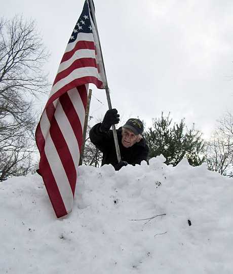 Only a  Marine (Don Knight) would raise the flag in the wake of the Blizzard of 2016. A seven foot pile of the white stuff in Kensington MD was scaled to get the banner in place  {Photo by Phyllis Knight)